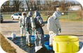 Four Men in HazMat Suits Processing Materials Outside on a Tarp