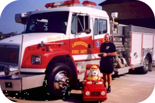 Man standing with Sparky the Dog in Front of a Fire Engine